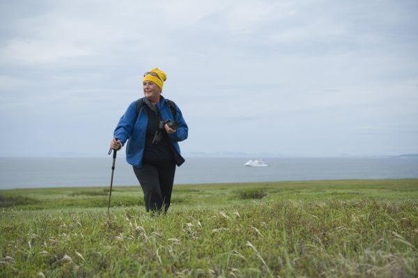 Tourist Female hiker walking, exploration on Bering Islands (Bering Sea) Russia, Asia